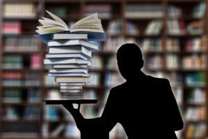 człowiek w bibliotece trzymajacy stos ksiazek