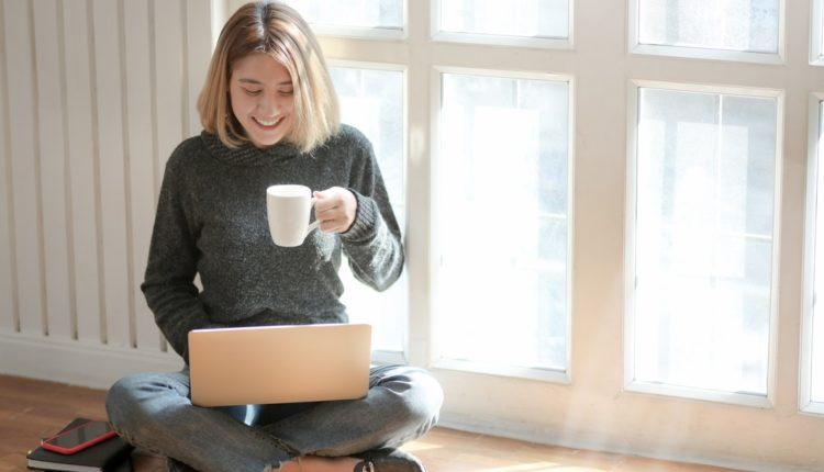 kobieta siedzi na podłodze pracuje pije kawe